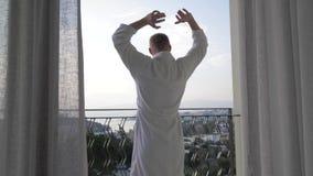 Um homem adulto em uma banheira branca vai ao balcão do hotel, endireita seus braços ao lado, aprecia a vista 4K video estoque