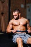 Um homem adulto muscular que faz exercícios em um simulador em um fundo do gym Aptidão, esportes, e conceito saudável do estilo d fotografia de stock royalty free