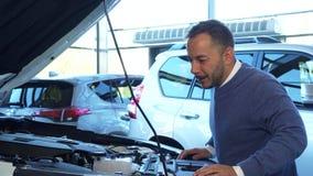 Um homem alegre abriu a capa do carro e estudou o que está para dentro imagens de stock royalty free