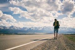 Um homem anda ao longo de uma estrada asfaltada que negligencia as montanhas fotos de stock royalty free