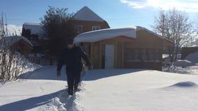Um homem anda através das grandes trações da neve na natureza e salta na neve em um fundo de casas cobertos de neve HD filme