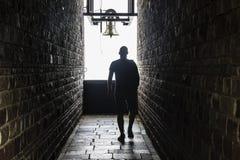 Um homem anda em um túnel escuro, mas em mostras de uma luz na extremidade Fotografia de Stock