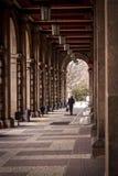 Um homem anda entre as colunas de uma grande construção velha um túnel formado por grandes colunas Fotos de Stock Royalty Free
