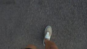 Um homem anda no asfalto nas sapatilhas marrons Vista de acima video estoque