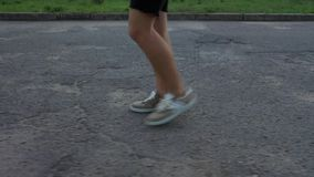 Um homem anda no asfalto nas sapatilhas marrons Vista lateral video estoque