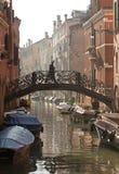 Um homem anda sobre uma ponte do canal no amanhecer Fotografia de Stock Royalty Free