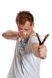 Um homem aponta um slingshot Fotografia de Stock Royalty Free