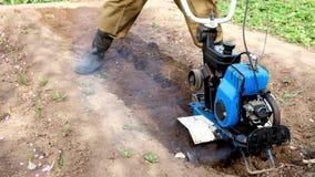Um homem ara a terra com um cultivador video estoque