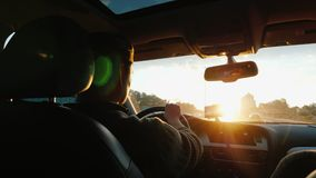 Um homem asiático conduz um carro ao longo da estrada, o sol de ajuste brilha no para-brisa Vista traseira foto de stock