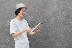 Um homem asiático criativo atractive novo com chapéu e vidros do fedora que aponta no tablet pc e no sorriso imagens de stock