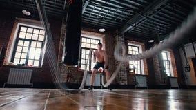 Um homem atl?tico no treinamento no gym Treinando suas m?os com batida das cordas vídeos de arquivo