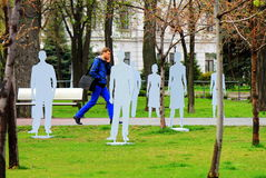 Um homem atravessa o parque entre as silhuetas que representam as vítimas do tráfico e da indiferença no telefone Fotos de Stock Royalty Free