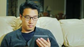 Um homem authenticAsian novo com vidros Está sentando-se no sofá em casa, lendo o eBook filme