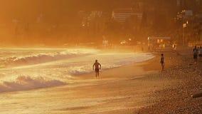 Um homem banha-se nas ondas em uma tempestade Por do sol filme