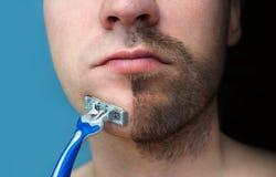 Um homem barbeia sua cara sem creme ou espuma, experimentando a dor e sofrendo A meia cara barbeou parcialmente coberto de vegeta fotos de stock