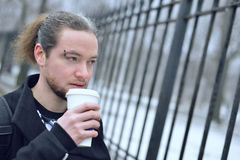 Um homem bebe o café de um copo na rua Imagens de Stock Royalty Free