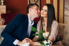 Um homem beija uma mulher em um restaurante sobre o jantar fotos de stock