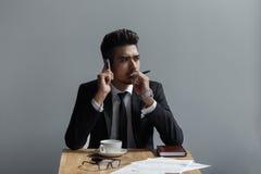 Um homem bem sucedido bonito que fala no escritório do telefone no café Imagem de Stock