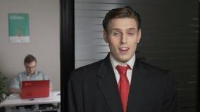 Um homem bem sucedido novo em um terno mostra uma emoção da surpresa, um retrato O homem trabalha em um computador no fundo 60 video estoque