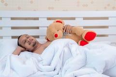 Um homem bonito dorme inocentemente na cama antes do trabalho foto de stock
