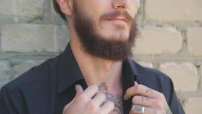 Um homem brutal considerável com uma barba nas calças de brim e em um t-shirt preto no fundo de uma parede de tijolo cinzenta filme