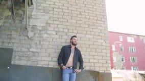 Um homem brutal considerável com uma barba nas calças de brim e em um t-shirt preto no fundo de uma parede de tijolo cinzenta video estoque