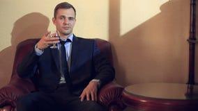 Um homem brutal em um terno senta-se em uma cadeira de couro com um vidro do álcool, olha a câmera video estoque