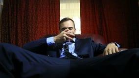 Um homem brutal em um terno senta-se em uma cadeira de couro com um vidro do álcool, olha a câmera vídeos de arquivo