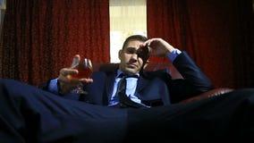 Um homem brutal em um terno senta-se em uma cadeira de couro com um vidro do álcool, olha a câmera filme