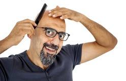 Um homem calvo com pente fotografia de stock