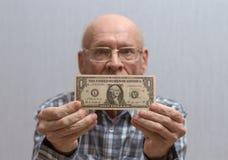 Um homem calvo idoso com vidros guarda uma c?dula na frente dele - um d?lar americano foto de stock royalty free