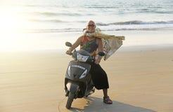 Um homem calvo monta em um 'trotinette' ao longo do litoral ou do b fotos de stock royalty free