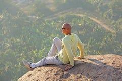Um homem calvo novo senta-se sobre uma montanha contra um fundo Imagens de Stock Royalty Free