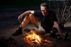 Um homem cansado com vidros aproxima a fogueira Imagens de Stock Royalty Free