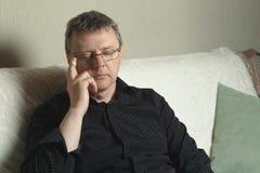 Um homem cansado com vidros está sentando-se no sofá imagens de stock royalty free