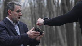 Um homem caucasiano branco com capa ameaça um homem no terno com uma arma e rouba o dinheiro da carteira video estoque