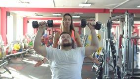Um homem caucasiano com uma barba executa um exercício nos pesos do banco do gym que sentam-se com a ajuda de uma menina bonita video estoque