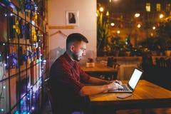 Um homem caucasiano considerável novo com barba e sorriso toothy em uma camisa quadriculado vermelha está trabalhando atrás de um foto de stock