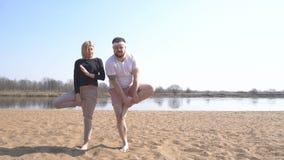 Um homem caucasiano e um instrutor da mulher são contratados na ioga dinâmica no banco de rio na natureza, técnicas meditativos vídeos de arquivo