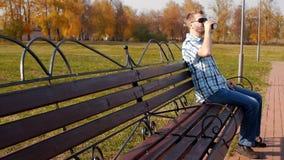 Um homem caucasiano novo em vidros pretos senta-se em um parque em um banco e em bebidas café, lento-mo, à moda, espaço da cópia video estoque