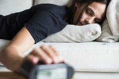 Um homem caucasiano sonolento que desliga um alarme fotos de stock