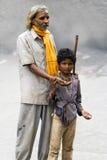 Um homem cego que implora pelo dinheiro com a ajuda de um menino novo - Índia fotografia de stock royalty free