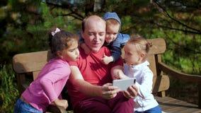Um homem com as crianças fotografadas em um smartphone que senta-se em um banco Família feliz que toma o selfie no parque Família vídeos de arquivo