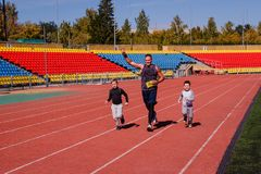 Um homem com as duas crianças que correm para o estádio dos esportes imagem de stock