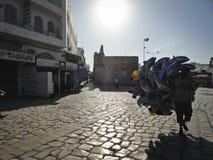 Um homem com balões está andando em um quadrado cobbled no luminoso fotografia de stock