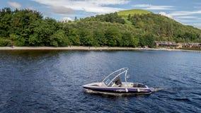 Um homem com um barco da velocidade no lago Lomond que procura turistas interrested para um passeio, lago Lomond, Escócia imagem de stock royalty free
