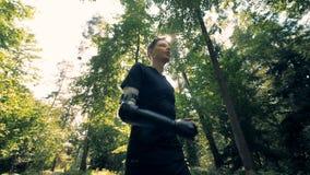 Um homem com um braço artificial está correndo ao longo da aleia Conceito humano futurista do cyborg