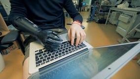 Um homem com braço protético está datilografando no teclado video estoque