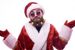 um homem com brinquedos do Natal em uma barba e em um terno de Santa Claus espalha seus braços na surpresa imagem de stock royalty free