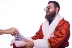 Um homem com brinquedos do Natal em uma barba e em um terno de Santa Claus realiza em suas mãos um chapéu de ano novo em que o la fotografia de stock